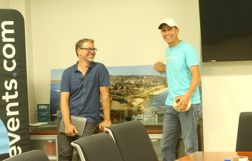 Events.com co-founders Stephen Partridge and Mitch Thrower pose by a photo of La Jolla displayed in their board room.