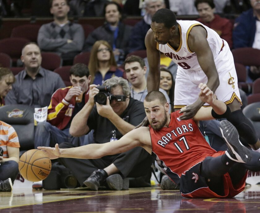 Toronto Raptors' Jonas Valanciunas (17), from Lithuania, stretches for the ball under pressure from Cleveland Cavaliers' Luol Deng, (9) from Sudan, during the first quarter of an NBA basketball game Tuesday, Feb. 25, 2014, in Cleveland. (AP Photo/Tony Dejak)
