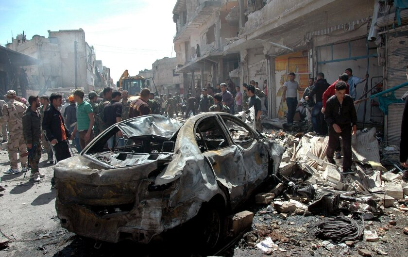 In this photo released by the Syrian official news agency SANA, Syrian people gather at the site of one of two car bombs that exploded in the pro-government district of Zahra in the central Syrian city of Homs, Syria, Tuesday, April 29, 2014. Dozens of people were killed and wounded in the attacks just hours after one of the deadliest mortar strikes in the heart of the capital, Damascus, killed 14, officials and state media said. (AP Photo/SANA)