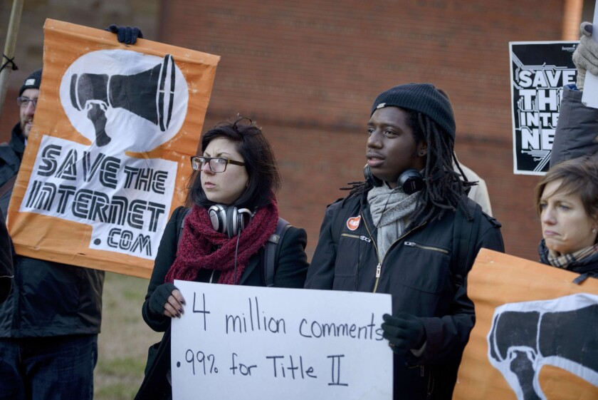Activists gather outside the headquarters of the Federal Communications Commission in Washington on Dec. 11 to urge tough net neutrality regulations.