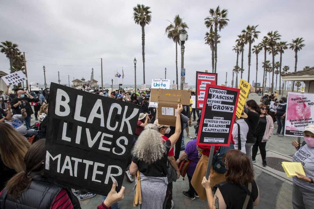 Protesters hold signs at a rally with palm trees in the background