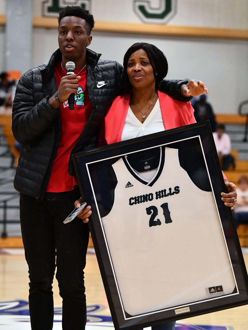Former Chino Hills standout Oneyka Okongwu with his mother, Kate, on Friday night during a ceremony to retire his jersey.