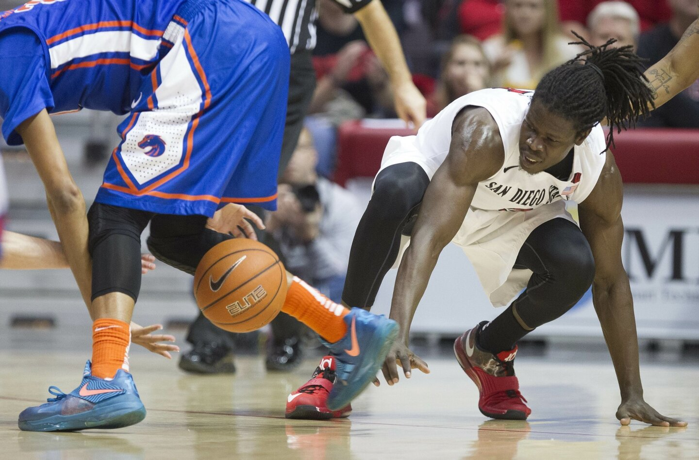 San Diego State vs. Boise State Men's Basketball at Viejas Arena. San Diego State Aztecs forward Angelo Chol (3) battles for a loose ball on the ground in the first half.
