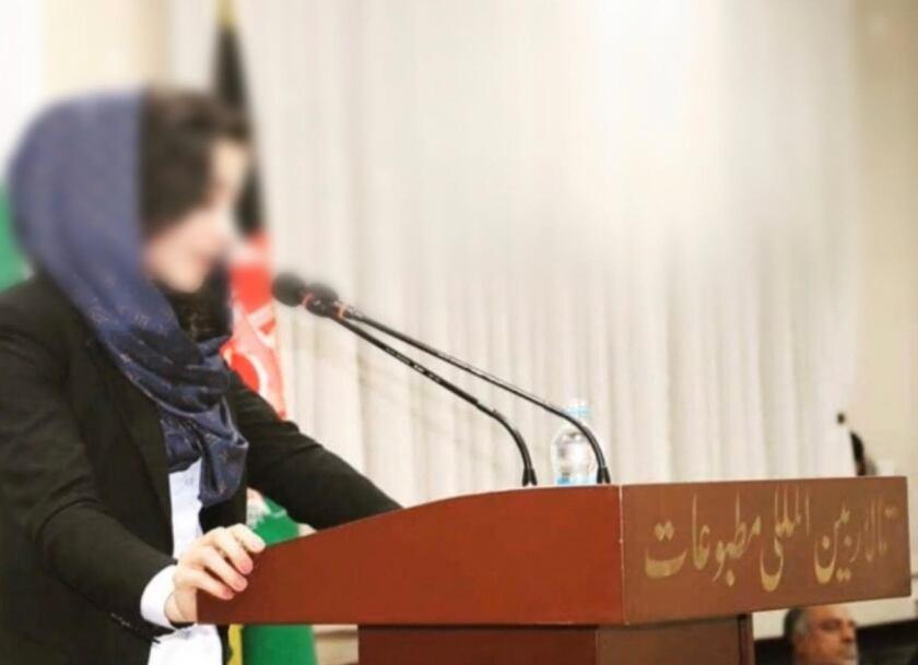 زنی با روسری روی سر ، با چهره ای تیره ، با میکروفون کنار دفتر ایستاده است