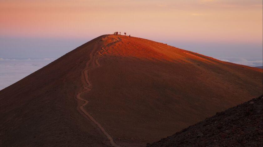 Visitors watching sunset from cinder cone called Puu Wekiu, summit of Mauna Kea