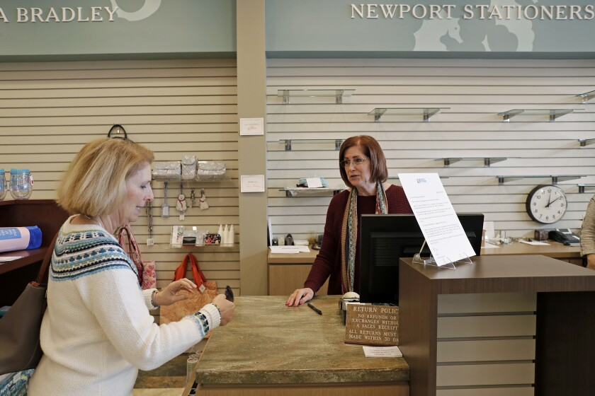 Co-manager Peggy Tackman, right, talks with longtime customer Lynda Badum on Friday at Newport Stationers in Corona del Mar. The store is having a liquidation sale as it prepares to close later this month.