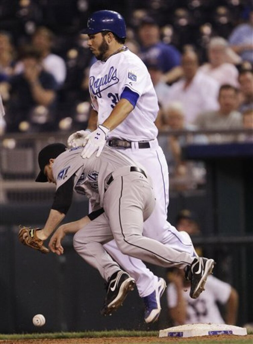 Toronto Blue Jays relief pitcher Jason Frasor (54) is knocked over by Kansas City Royals' Eric Hosmer (35) as he tries to cover first base during the tenth inning of a baseball game in Kansas City, Mo., Monday, June 6, 2011. Hosmer was safe with a single. (AP Photo/Orlin Wagner)