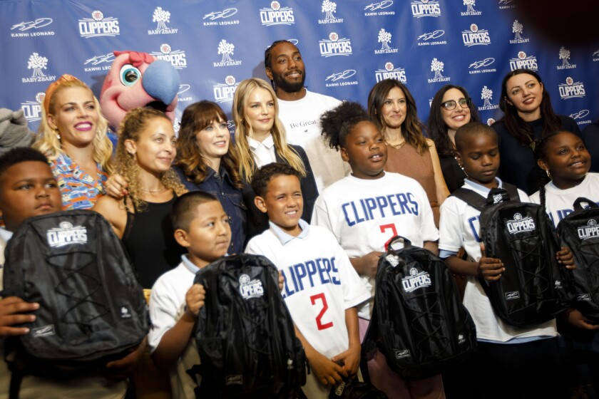 Clippers Kawhi Leonard stands with representatives from Baby 2 Baby as he gives backpacks away to students at One Hundred Seventh Street Elementary School on Tuesday in the Watts neighborhood of Los Angeles.