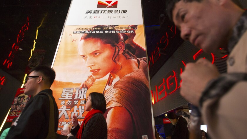 """People walk past a poster for Disney's """"Star Wars"""" film at a movie theater in Beijing on Jan. 9."""