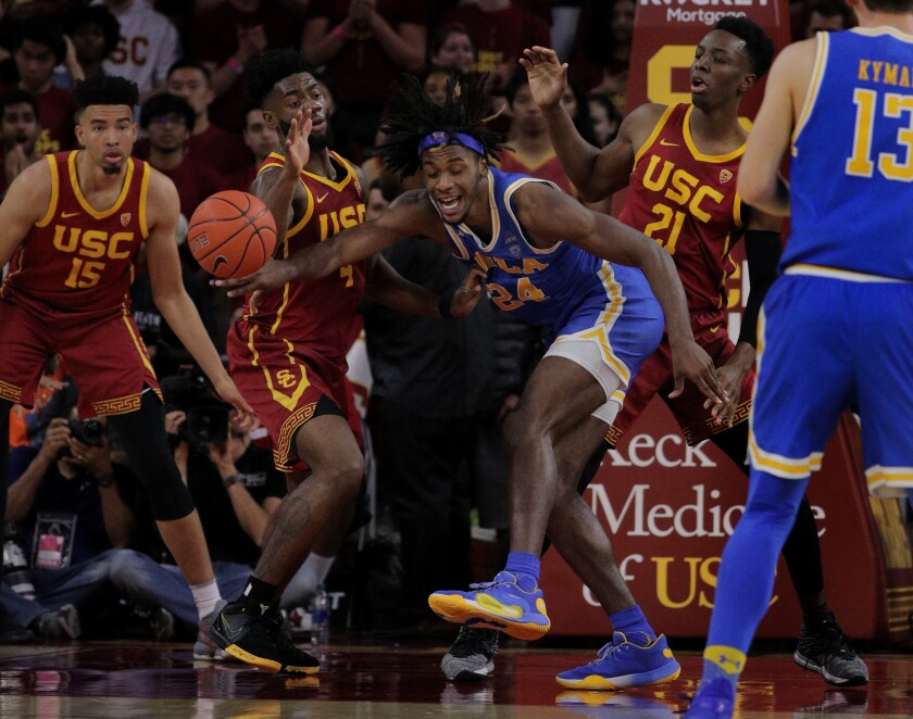 UCLA forward Jalen Hill (24) loses the ball as he's triple teamed by USC's Isaiah Mobley (15), Daniel Utomi (4), and Onyeka Okongwu (21) during the second half of a game March 7, 2020, at Galen Center.