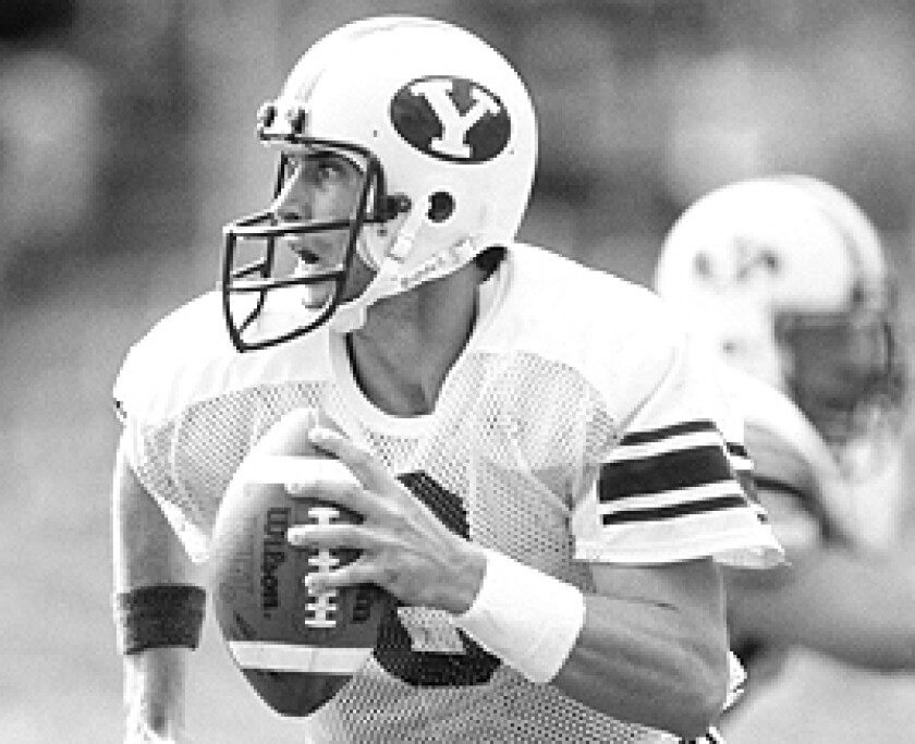 Quarterback Steve Young of the Brigham Young University Cougars runs with the ball as he looks down field for a receiver during a 1983 NCAA game.