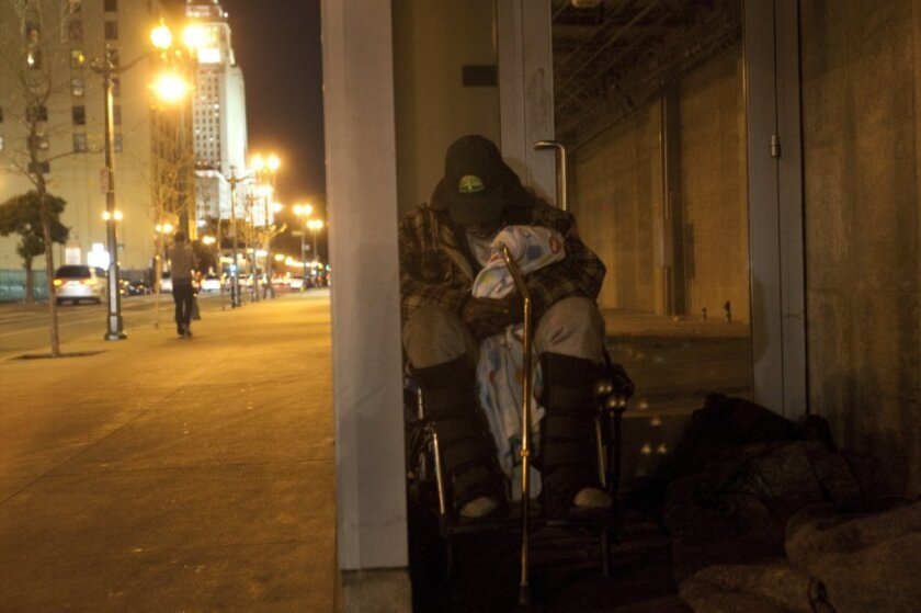With L.A. City Hall in view, a homeless man sleeps in a doorway in downtown L.A.