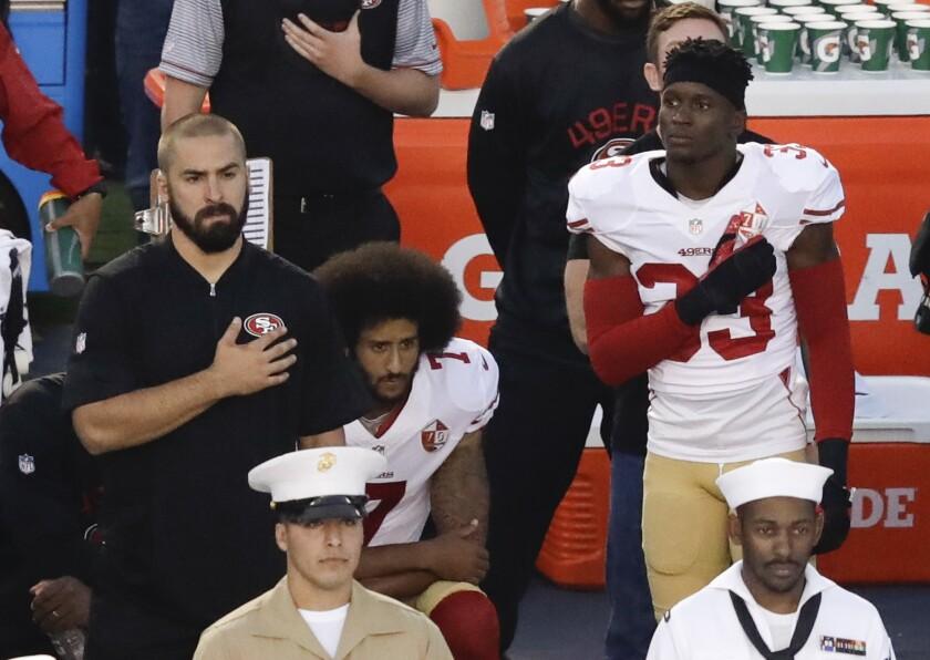 San Francisco 49ers quarterback Colin Kaepernick (7) kneels during the national anthem before a preseason game in San Diego.
