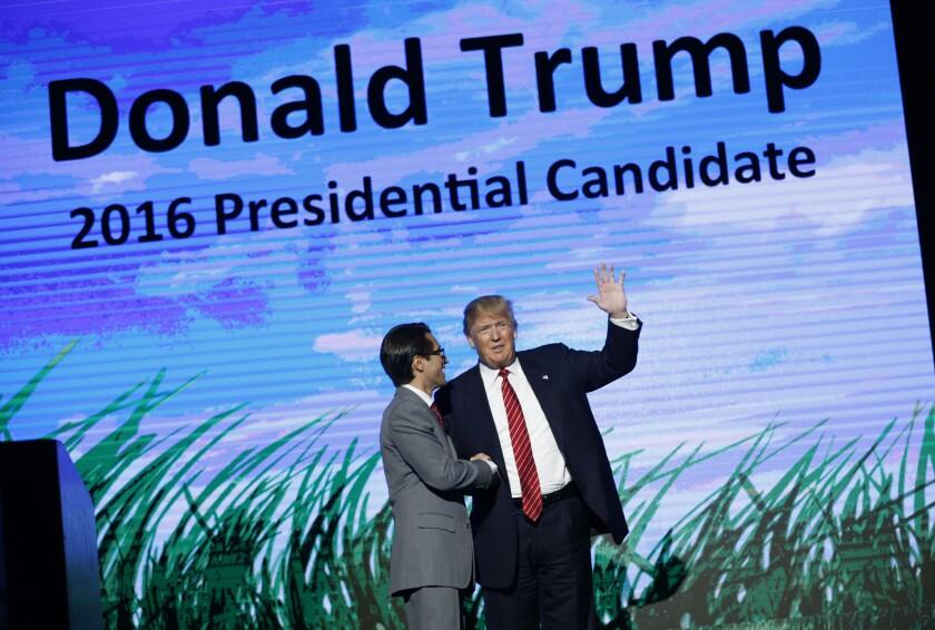 El magnate Donald Trump, derecha, aspirante a la candidatura republicana a la presidencia, saluda desde el escenario del Freedomfest, el sábado 11 de julio de 2015, en Las Vegas. (Foto AP/John Locher)