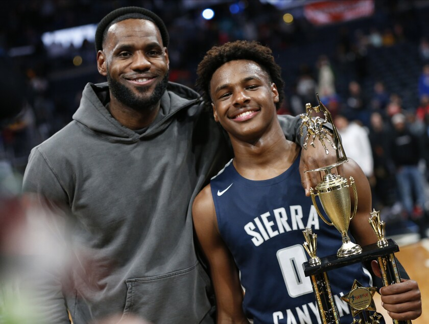 LeBron James poses for photos with son Bronny after Sierra Canyon High defeated the Lakers' star's alma mater on Dec. 14, 2019, in Columbus, Ohio.