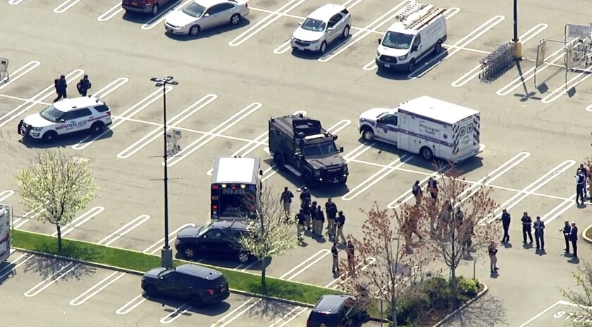 An aerial view of a parking lot where emergency vehicles and law enforcement are gathered.
