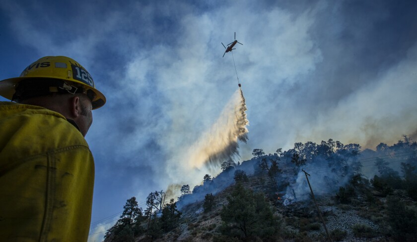 A firefighter looks up at a huge plume of water falling from a helicopter