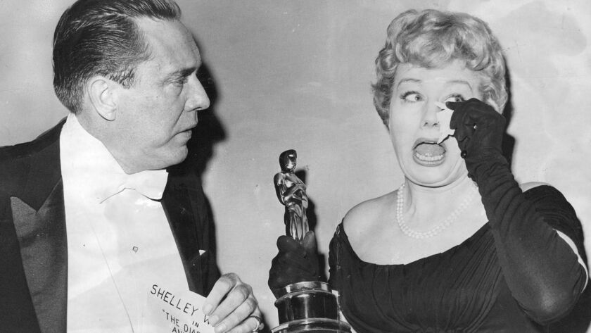 """Actress Shelley Winters bursts into tears as she accepts the 1960 Oscar for best supporting actress from actor Edmond O'Brien. Winters won for her role in """"Diary of Anne Frank."""""""