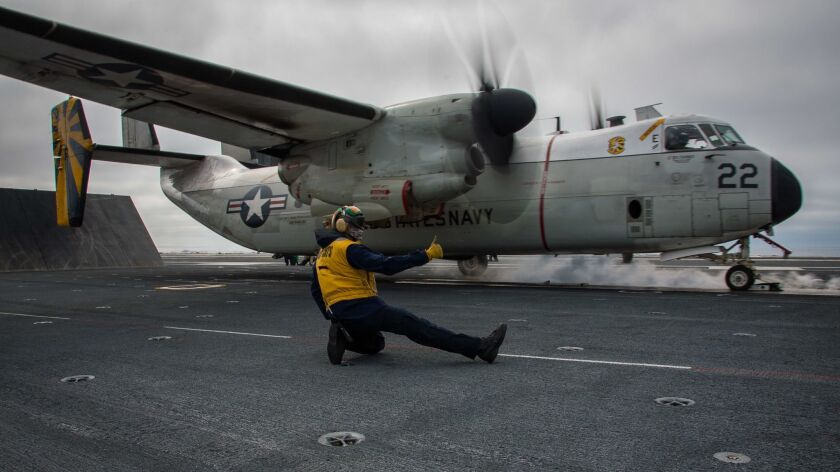 """Aviation Boatswain's Mate 2nd Class Chad Cole on Feb. 10 signals for a C-2A Greyhound logistics aircraft assigned to the """"Providers"""" of Fleet Logistics Support Squadron 30 to take off from the North Island-based carrier Theodore Roosevelt."""