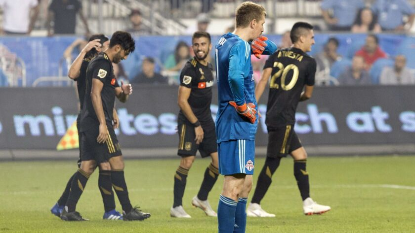 Toronto FC goalkeeper Clint Irwin reacts as Los Angeles FC's Carlos Vela, left, is congratulated aft