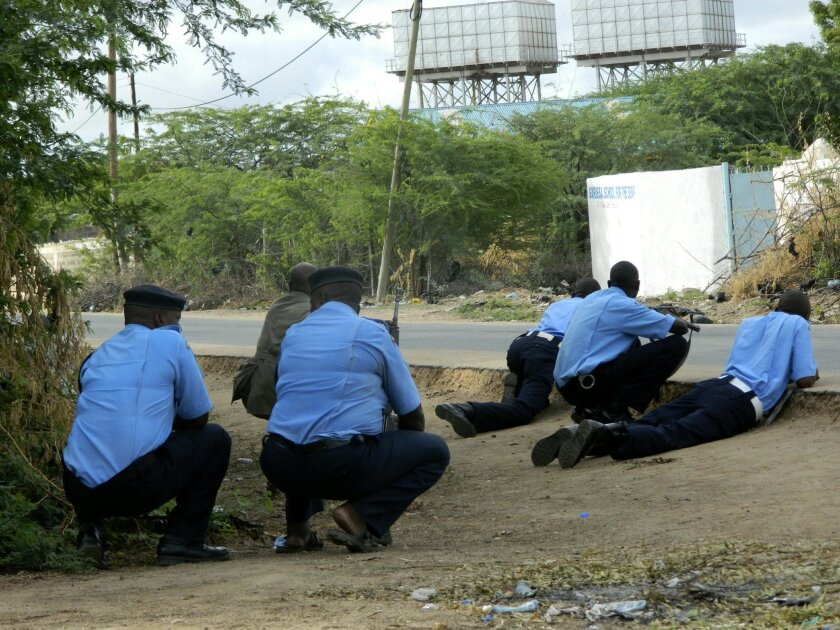 Kenyan police officers take cover outside the Garissa University College during an attack by gunmen in Garissa, Kenya, Thursday, April 2, 2015. Gunmen attacked the university early Thursday, shooting indiscriminately in campus hostels. Police and military surrounded the buildings and were trying to