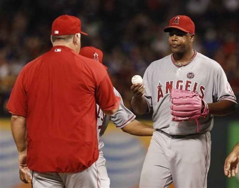 Los Angeles Angels starting pitcher Jerome Williams, right, hands the ball over to manager Mike Scioscia, left, after being relieved of his duties against the Texas Rangers during the eighth inning of a baseball game, Wednesday, July 31, 2013, in Arlington, Texas. The Rangers won 2-1. (AP Photo/Jim Cowsert)