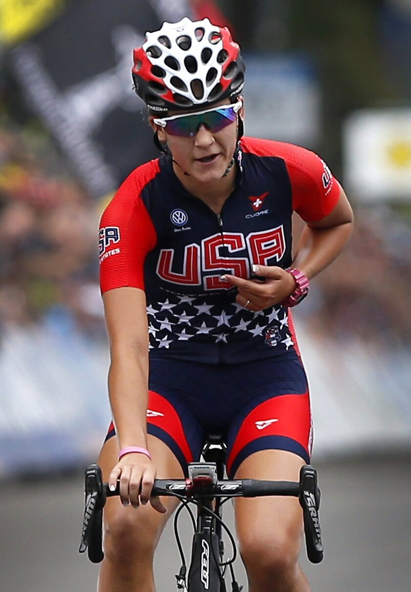 FILE - In this Sept. 25, 2015, file photo, Chloe Dygert points to the USA lettering on her jersey as she crosses the finish line of the Women's Junior Road Circuit cycling race at the UCI Road World Championships in Richmond, Va., Friday, Sept. 25, 2015, Four years ago, Chloe Dygert's cycling exper