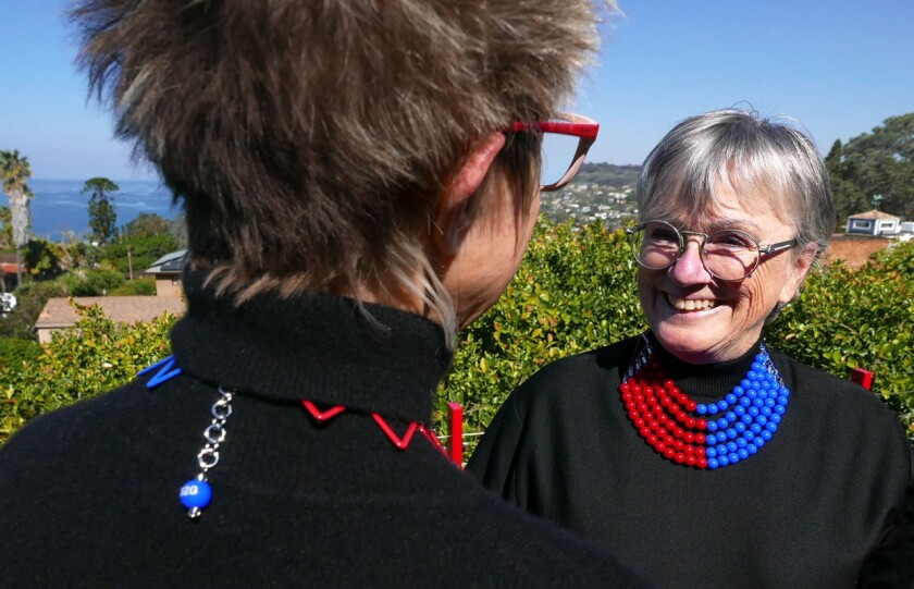 Christine Forester, right, chats with her friend Dale Steele. Both women are wearing the 51/49 political necklace Forester designed. It depicts the U.S. Senate seating chart as she would like to see it, with blue seats (Democrats) outnumbering red seats (Republicans).