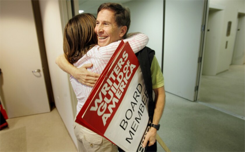 END IN SIGHT: Board members Robin Schiff, left and Tom Schulman embrace moments before a press conference announcing the potential end to the WGA strike.