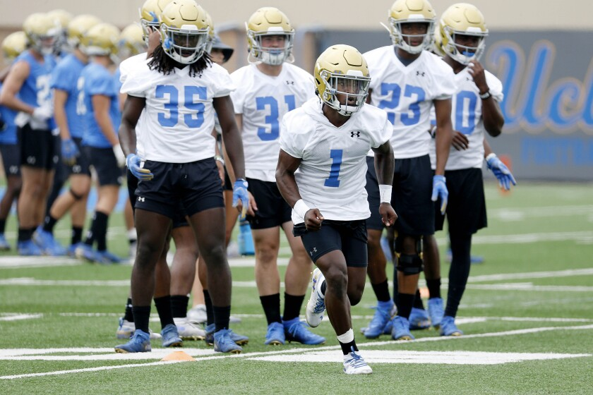 UCLA's Darnay Holmes (1), along with teammates, runs through drills at fall camp practice at the Wasserman Football Center on the campus of UCLA on Wednesday.