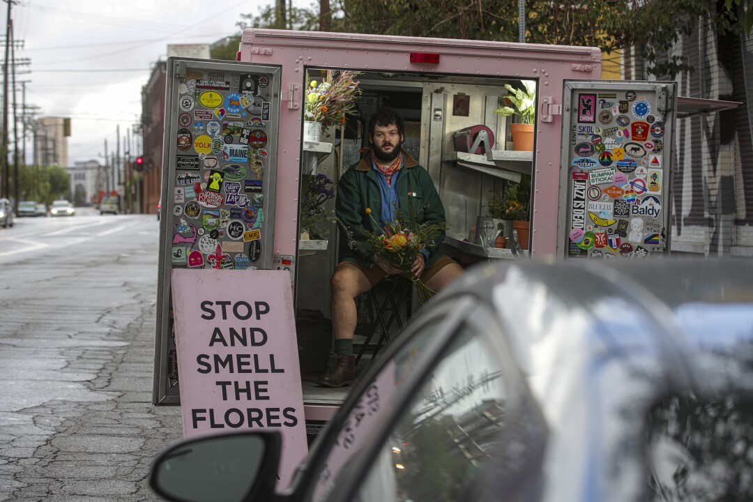 """A man sits in the back of an open, pink truck next to a sign reading """"Stop and Smell the Flores."""""""