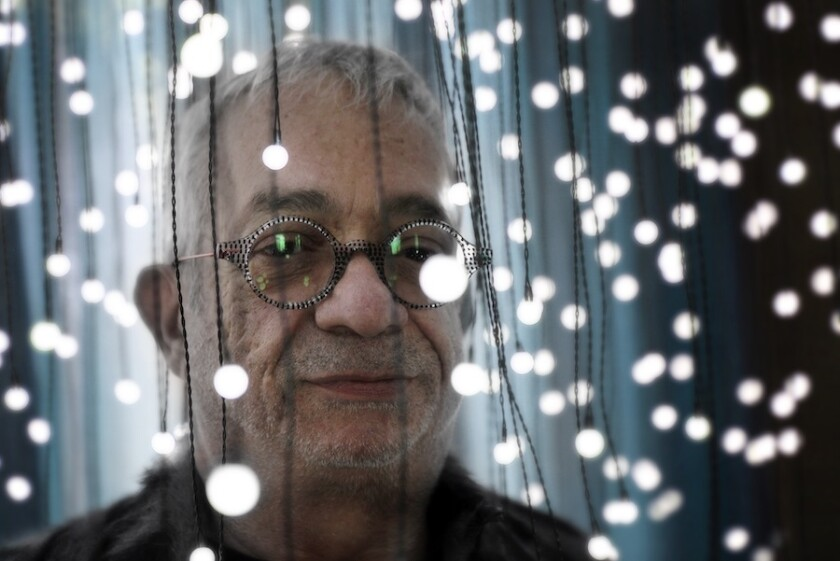 A man wearing round glasses stands under dangling string lights