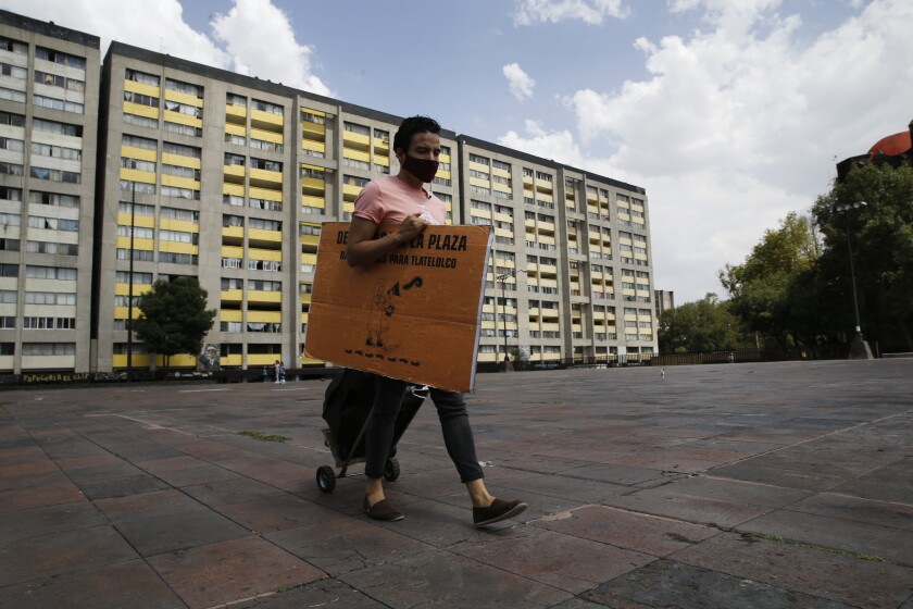 Percibald Garcia, who reads aloud children's books outside the high-rise buildings in the Tlatelolco housing complex, pulls a loudspeaker as he walks between buildings, in Mexico City, Saturday, July 18, 2020. Confinement during the coronavirus pandemic has been especially tedious for children, so the young architect sets out every afternoon with a microphone and a loudspeaker to walk the neighborhood where he lives and provide entertainment. (AP Photo/Marco Ugarte)