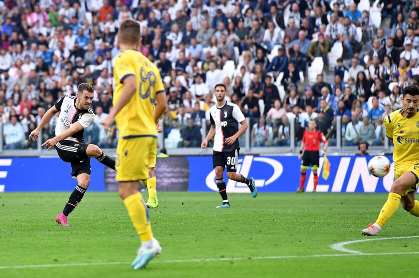 Juventus' Aaron Ramsey, left, scores his side first goal during the italian Serie A soccer match between Juventus and Verona at the Juventus' Stadium in Turin, Italy, Saturday, Sept. 21, 2019. (Alessandro Di Marco/ANSA via AP)