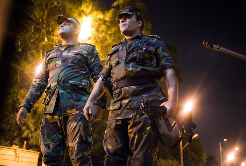 Egyptian army officers look on as as opponents of ousted President Mohamed Morsi celebrate.
