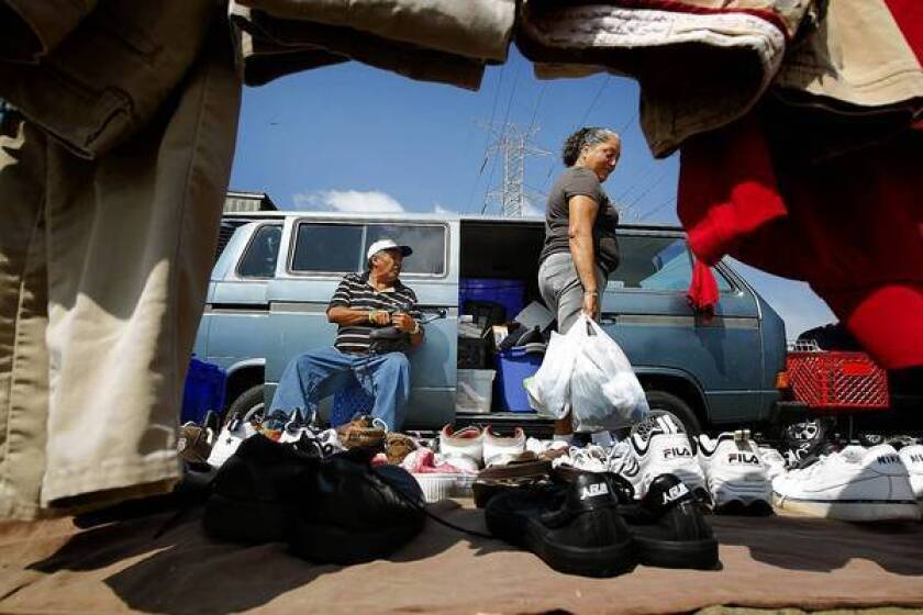 Jesus Navarro, left, looks on as a customer browses his items at an informal outdoor market in Watts. L.A. County Supervisor Mark Ridley-Thomas wants to crack down on such operations.