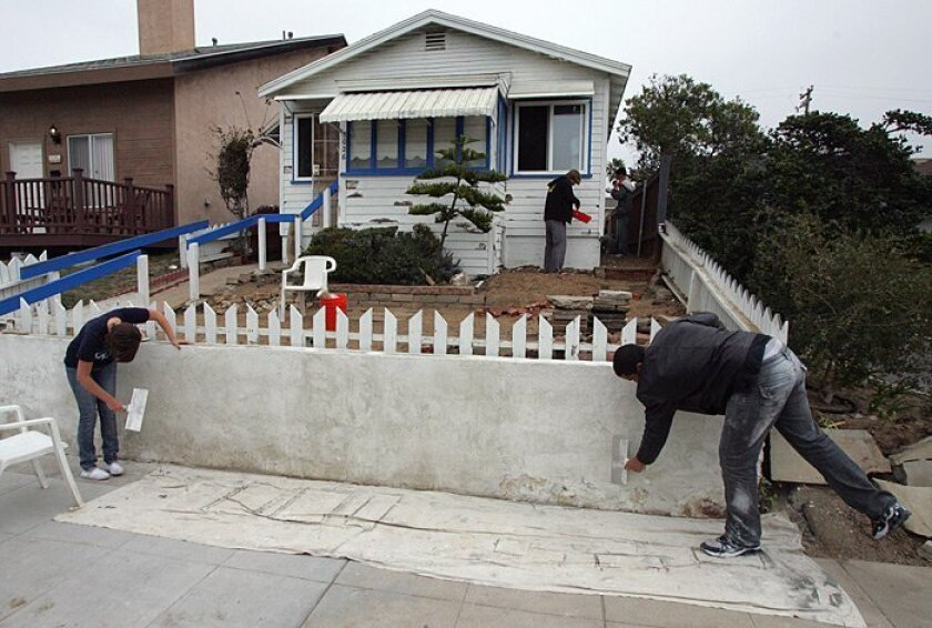 Maddie Piffard (left), 17, and Jensen Briley (right), 15, worked on the fence at the Ocean Beach home of instructor Josh Saxe on Wednesday during their intersession class on home design.