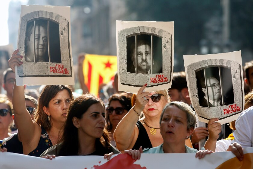 People hold portraits of some of the Catalan political leaders who were sentenced to prison after the Supreme Court delivered its sentence, in Barcelona.