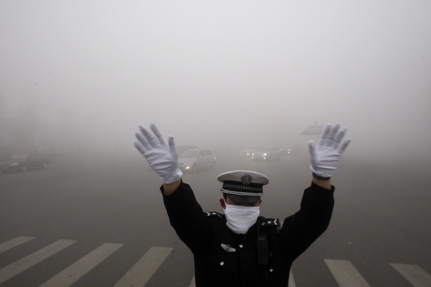 A policeman works on a pollution-shrouded street in Harbin, China.