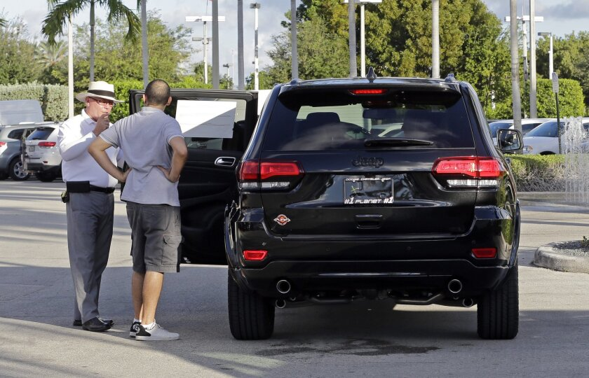 In this photo taken Thursday, Nov. 5, 2015, salesperson Andrew Montalvo, left, talks to customer who checks out the interior of a Grand Cherokee Limited in Doral, Fla. On Tuesday, May 31, 2016, the Conference Board releases its May index on U.S. consumer confidence. (AP Photo/Alan Diaz)