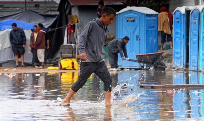 Integrantes de la caravana de migrantes centroamericanos tratan de protegerse luego de que el albergue en el que se concentraban se inundara por las fuertes lluvias hoy en Tijuana (México). EFE