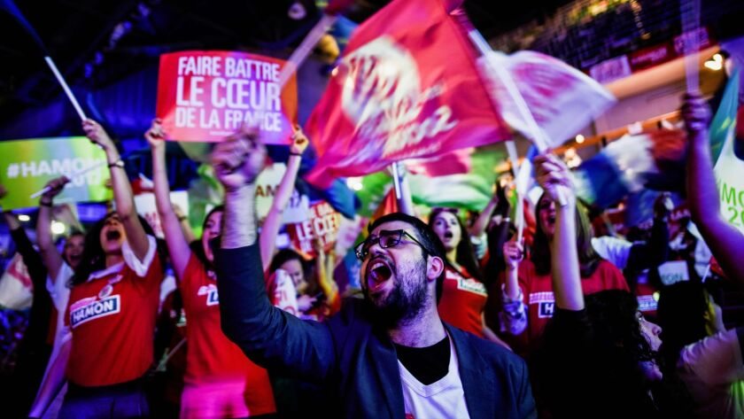 Supporters of French presidential election candidate for the left-wing French Socialist Party Benoit Hamon wave flags as they attend a campaign meeting in Villeurbanne, near Lyon, central-eastern France, on April 11, 2017.