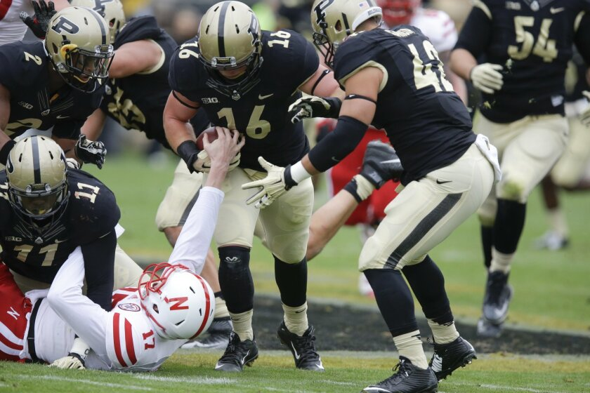 Nebraska quarterback Ryker Fyfe (17) tries to strip the ball from Purdue linebacker Garrett Hudson (16) after Hudson recovered a fumble during the first half of an NCAA college football game in West Lafayette, Ind., Saturday, Oct. 31, 2015. (AP Photo/Michael Conroy)