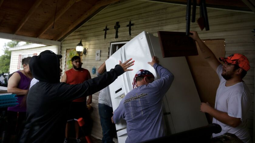 The Gonzalez family lift a refrigerator as they prepare to evacuate their home on the banks of the B