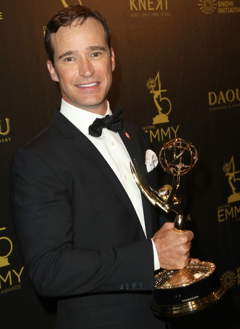 A man in a tuxedo holds an Emmy Award