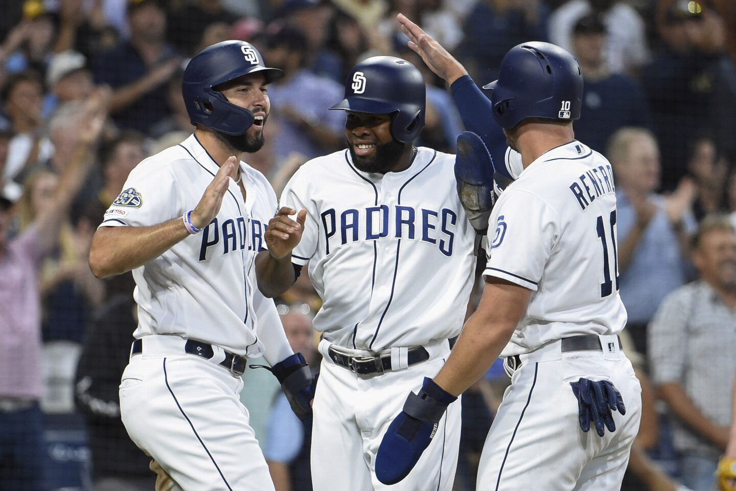 SAN DIEGO, CA - AUGUST 13: Manuel Margot #7 of the San Diego Padres (C) is congratulated by Eric Hosmer #30 (L) and Hunter Renfroe #10 after scoring during the first inning of a baseball game against the Tampa Bay Rays at Petco Park August 13, 2019 in San Diego, California. (Photo by Denis Poroy/Getty Images) ** OUTS - ELSENT, FPG, CM - OUTS * NM, PH, VA if sourced by CT, LA or MoD **