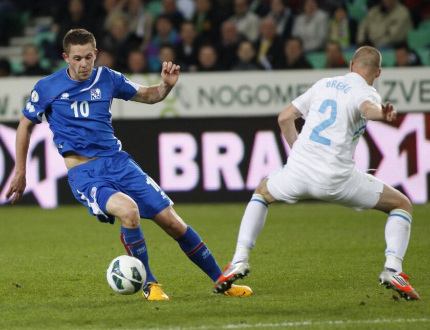 FILE - In this  Friday, March 22, 2013 filer, Iceland's Gylfi Thor Sigurdsson, left, is challenged by Slovenia's Miso Brecko during a World Cup group E qualifying  soccer match between Slovenia and Iceland in Ljubljana, Slovenia. (AP Photo/Filip Horvat, File)