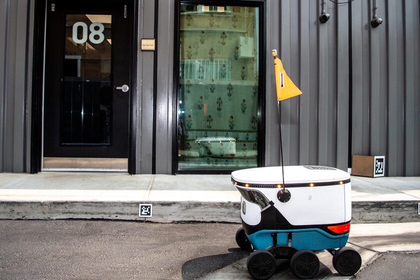 A small robot with six wheels and a yellow flag next to a curbside