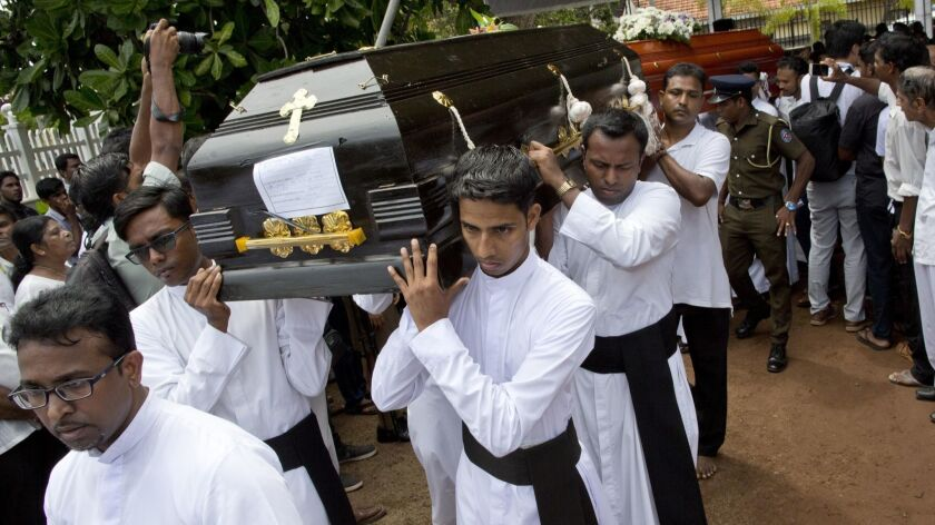 Clerics carry coffins during a funeral service April 23 for the Easter Sunday bomb blast victims at St. Sebastian Church in Negombo, Sri Lanka.
