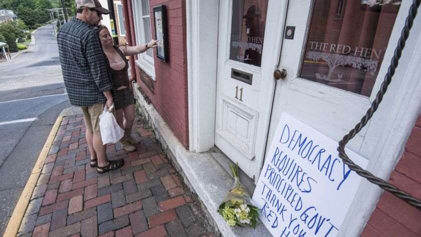 Passersby examine the menu at the Red Hen Restaurant Saturday, June 23, 2018, in Lexington, Va. Whit